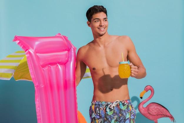 Lächelnder junger mann, der mit getränk und schwimmenmatratze im studio aufwirft