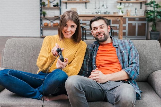 Lächelnder junger mann, der mit ihrer frau spielt videospiel sitzt