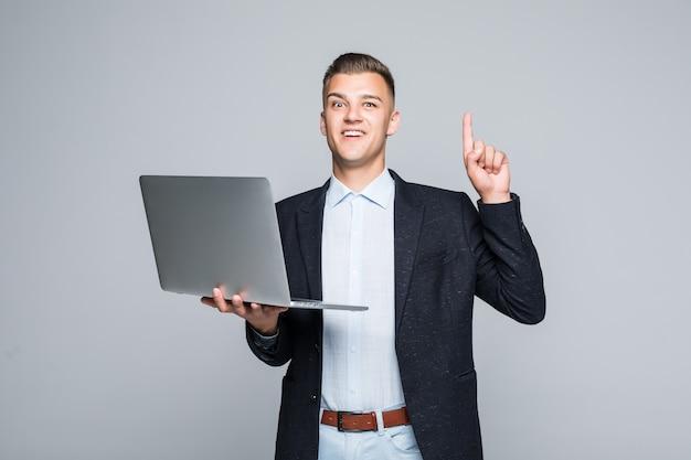 Lächelnder junger mann, der mit laptop-telefon posiert, das in der dunklen jacke im studio lokalisiert auf grauer wand gekleidet ist