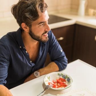 Lächelnder junger mann, der mit salatschüssel sitzt