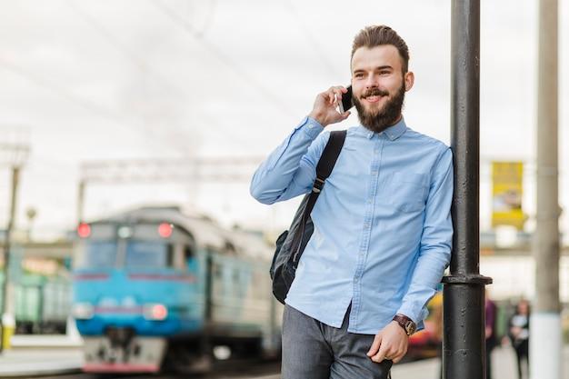 Lächelnder junger mann, der mobiltelefon am bahnhof verwendet
