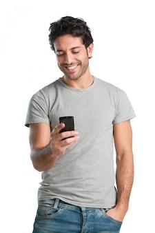 Lächelnder junger mann, der sein smartphone betrachtet, während textnachrichten lokalisiert auf weißem hintergrund