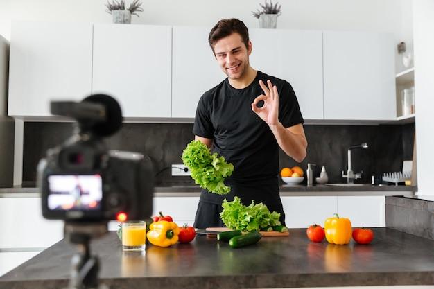 Lächelnder junger mann, der seine videoblogepisode filmt