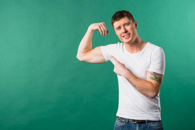 Lächelnder junger mann, der seinen muskulösen muskel gegen grünen hintergrund zeigt