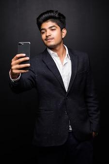 Lächelnder junger mann, der selfie foto auf smartphone nimmt