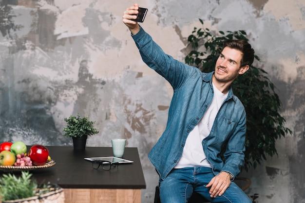 Lächelnder junger mann, der selfie vom mobiltelefon nimmt