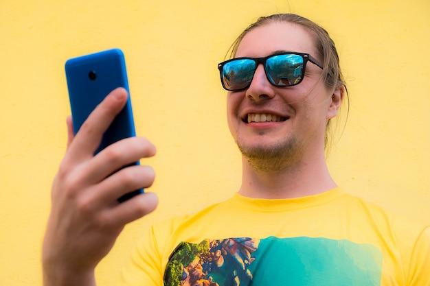 Lächelnder junger mann, der smartphone benutzt, um mit familie und freunden in kontakt zu treten
