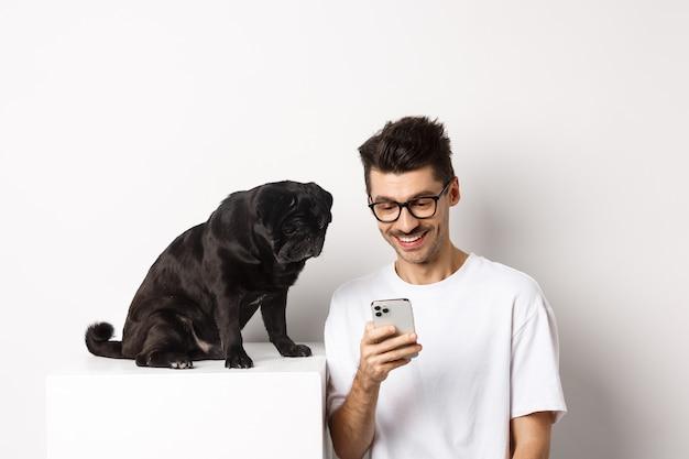 Lächelnder junger mann, der smartphone benutzt und nahe hund sitzt. mopsbesitzer prüft fotos auf handy, weiß