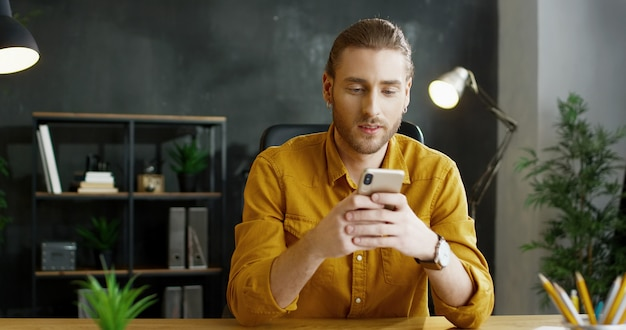 Lächelnder junger mann, der smartphone in den händen im büro hält.