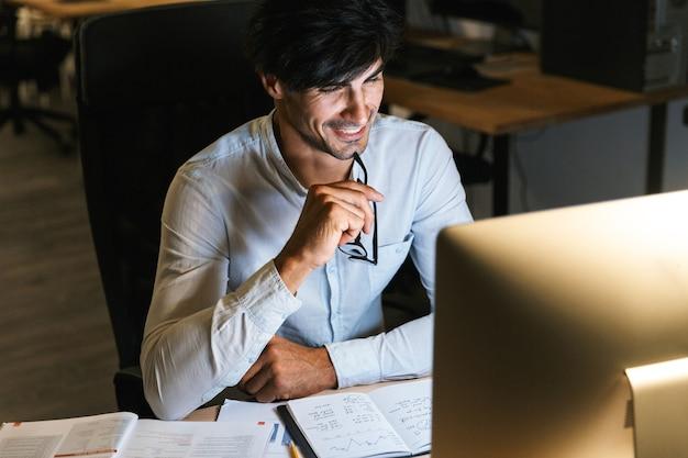 Lächelnder junger mann, der spät in der nacht im büro arbeitet