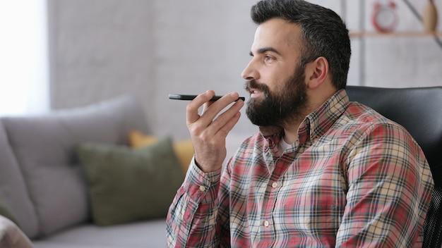 Lächelnder junger mann, der sprachnachrichten auf dem smartphone aufzeichnet, mit virtuellem assistenten, der zu hause sitzt.