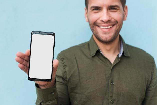 Lächelnder junger mann der stoppeln, der weißen smartphone des leeren bildschirms hält