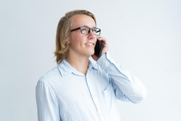 Lächelnder junger mann, der um smartphone ersucht