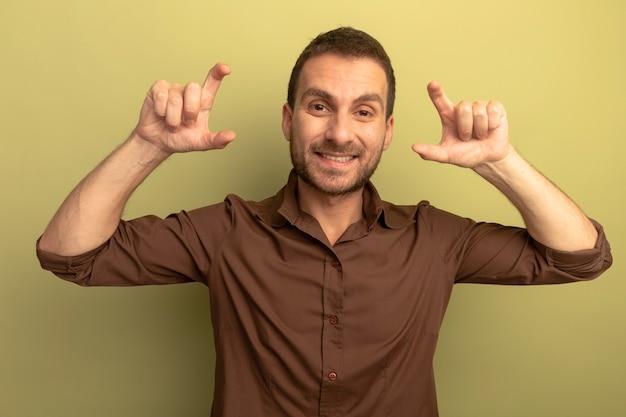 Lächelnder junger mann, der vorne schaut und kleine mengengeste tut, lokalisiert auf olivgrüner wand