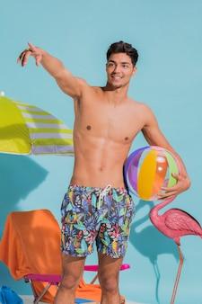 Lächelnder junger mann, der weg auf strand darstellt