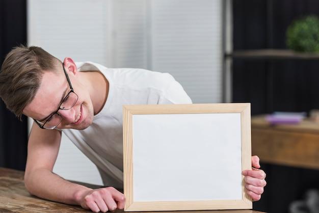 Lächelnder junger mann, der weißes hölzernes brett auf tabelle betrachtet