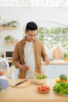 Lächelnder junger mann, der zu hause in der küche gemüsesalat macht