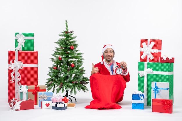 Lächelnder junger mann feiern neujahrs- oder weihnachtsfeiertag, der auf dem boden sitzt und uhr nahe geschenken und geschmücktem weihnachtsbaum hält