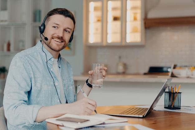 Lächelnder junger mann, freiberufler oder unternehmer, der von zu hause aus arbeitet und während einer online-konferenz ein headset mit mikrofon verwendet, ein glas wasser hält und beiseite schaut. remote-job-konzept