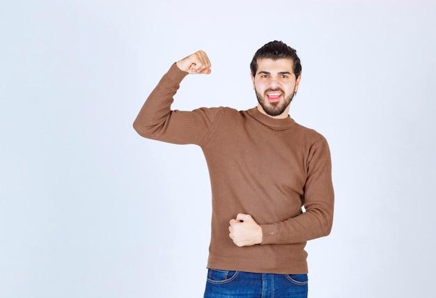 Lächelnder junger mann im pullover mit bizeps und blick in die kamera. foto in hoher qualität
