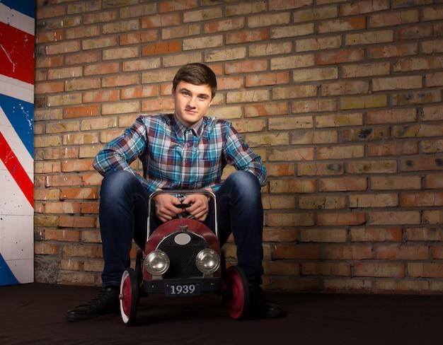 Lächelnder junger mann im trendigen outfit sitzt auf spielzeugautos, während er in die kamera schaut. innenaufnahme mit backsteinmauer-hintergrund.