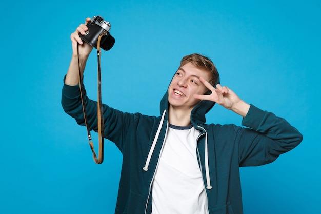Lächelnder junger mann in freizeitkleidung, der selfie auf retro-vintage-fotokamera macht und das siegeszeichen isoliert auf blauer wand zeigt. menschen aufrichtige emotionen, lifestyle-konzept.