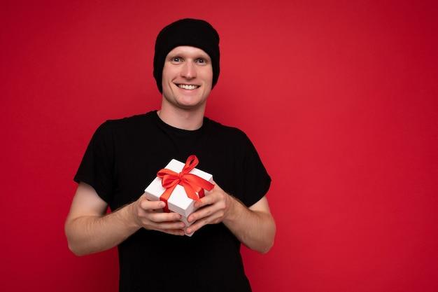 Lächelnder junger mann lokalisiert über roter hintergrundwand, die schwarzen hut und schwarzes t-shirt hält, das weiße geschenkbox mit rotem band hält und kamera betrachtet.