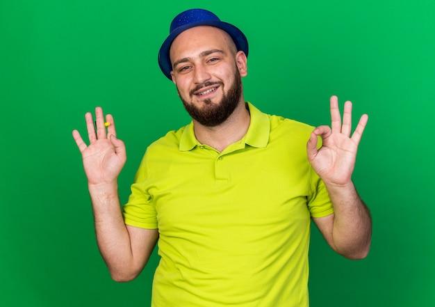 Lächelnder junger mann mit blauem partyhut, der eine partypfeife hält und die hand ausbreitet, die eine gute geste zeigt
