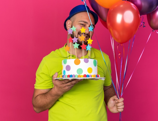 Lächelnder junger mann mit blauem partyhut, der luftballons mit kuchen hält