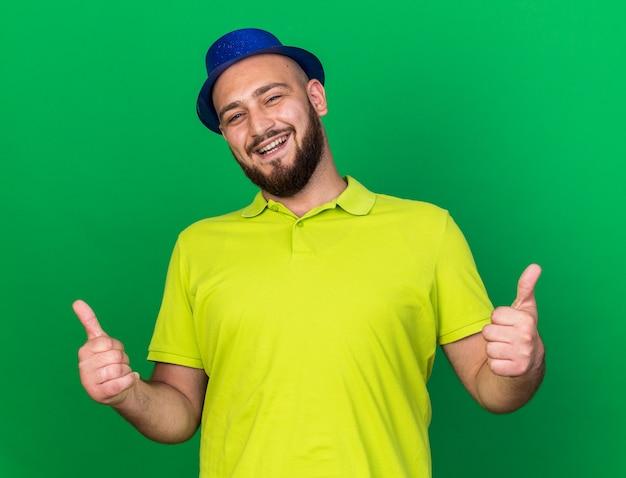 Lächelnder junger mann mit blauem partyhut zeigt daumen hoch