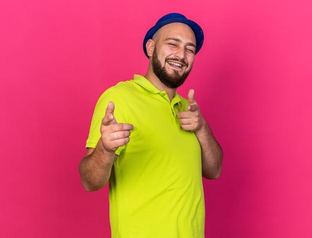 Lächelnder junger mann mit blauem partyhut zeigt in die kamera