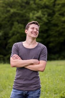 Lächelnder junger mann mit den armen kreuzte in der natur