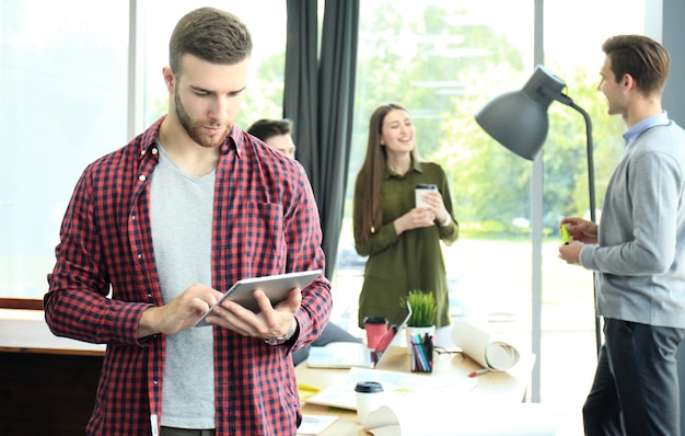 Lächelnder junger mann mit digitalem tablet im büro.