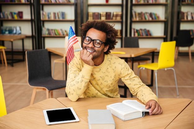 Lächelnder junger mann mit fahne, die buch in der bibliothek sitzt und liest