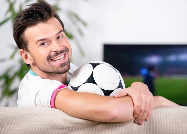 Lächelnder junger mann mit fußball beim aufpassen des spiels.