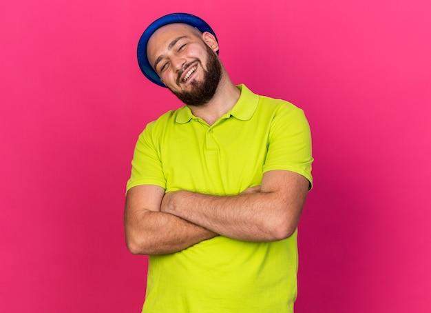 Lächelnder junger mann mit geneigtem kopf, der blauen partyhut trägt, der die hände kreuzt