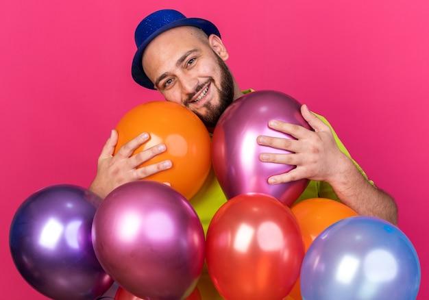 Lächelnder junger mann mit geneigtem kopf, der einen partyhut trägt, der hinter ballons steht, isoliert auf rosa wand