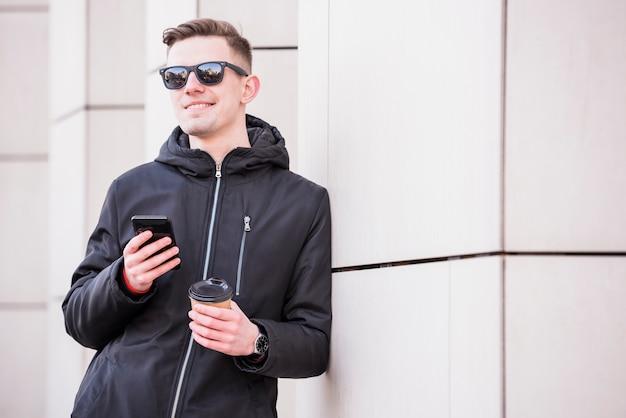 Lächelnder junger mann mit mobile in der hand halten mitnehmerkaffeetasse