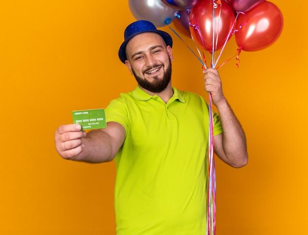 Lächelnder junger mann mit partyhut, der luftballons hält und die kreditkarte isoliert auf der orangefarbenen wand ausschaut
