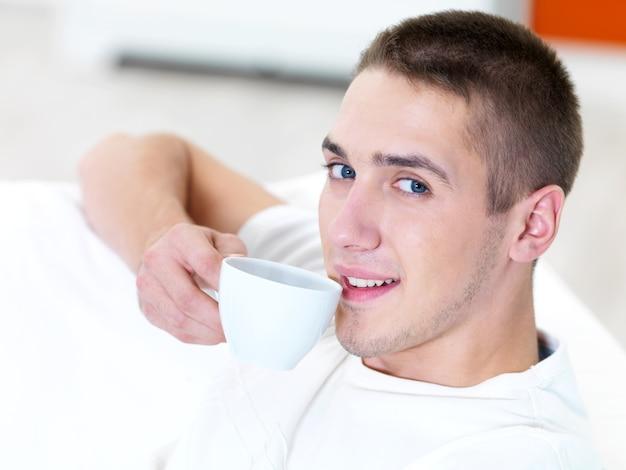 Lächelnder junger mann mit tasse kaffee zu hause