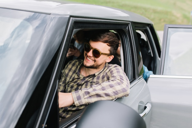 Lächelnder junger mann mit trendigem haarschnitt und bart, der mit familie mit dem auto durch italien reist