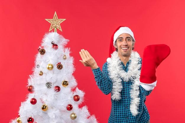 Lächelnder junger mann mit weihnachtsmannhut in einem blauen gestreiften hemd und tragen seiner weihnachtssocke nahe weihnachtsbaum auf rot