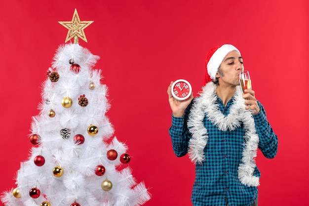 Lächelnder junger mann mit weihnachtsmannhut und verkostung eines glases wein und halten der uhr, die nahe weihnachtsbaum auf rot steht