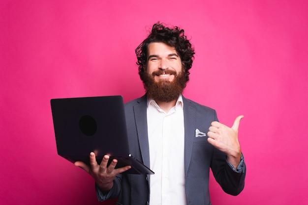 Lächelnder junger mann schaut auf die kamera, die einen daumen hoch und einen offenen computer nahe einer rosa wand hält