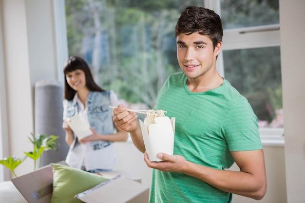 Lächelnder junger mann und frau, die zu hause nudeln essen