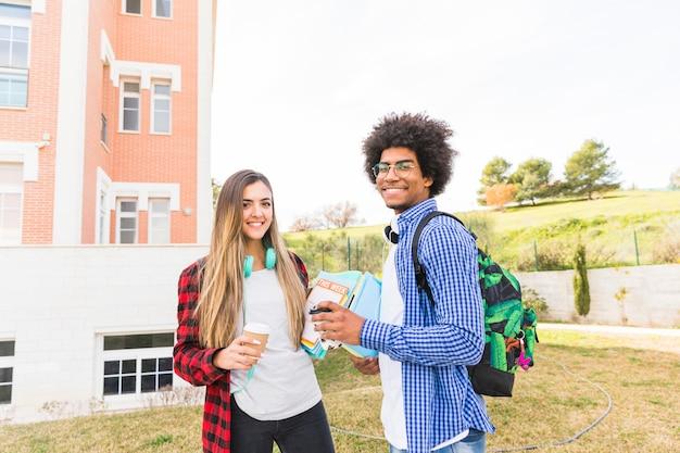 Lächelnder junger mann und studentinnen, die in der hand mitnehmerkaffeetasse und -bücher stehen am campus halten