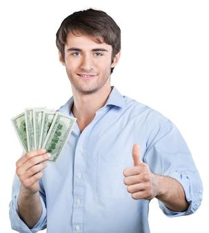 Lächelnder junger mann zeigt daumen hoch, während er geld hält