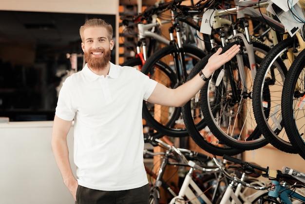Lächelnder junger mann zeigt reihe von modernen fahrrädern