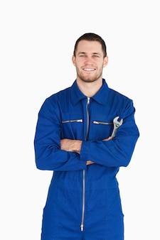 Lächelnder junger mechaniker in der kesselklage mit dem schlüssel und armen gefaltet