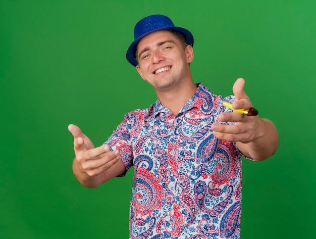Lächelnder junger partei-typ, der blauen hut hält, der partygebläse hält und hände an der kamera lokalisiert auf grünem hintergrund hält